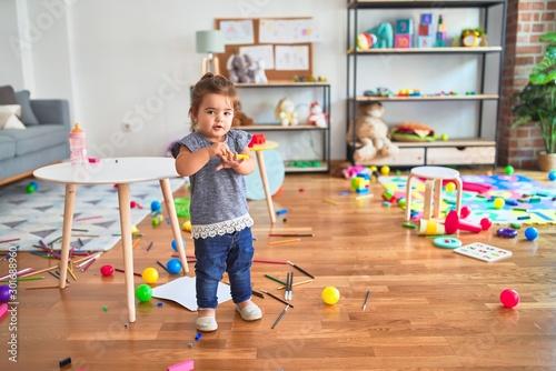 Obraz Beautiful toddler holding yellow pen standing around lots of toys smiling at kindergarten - fototapety do salonu