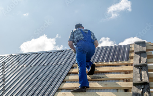 Photo  male builder performs work on the roof, fastens corrugated sheets О