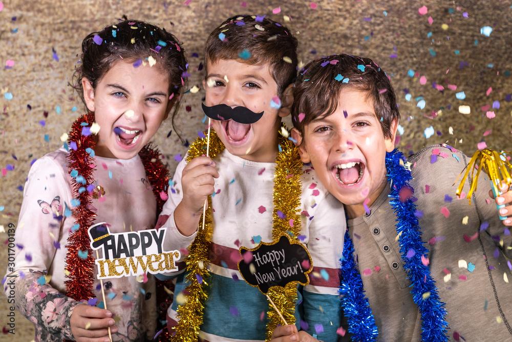 Fototapety, obrazy: Thre happy kids celebrating new year eve at home