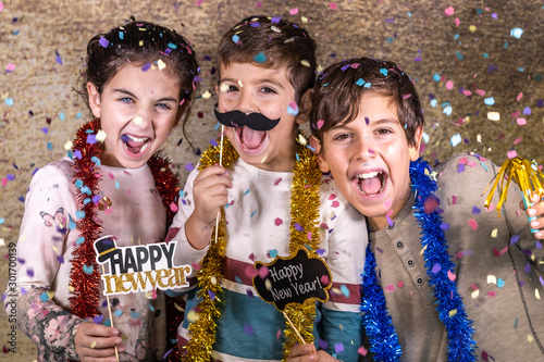Thre happy kids celebrating new year eve at home Wallpaper Mural