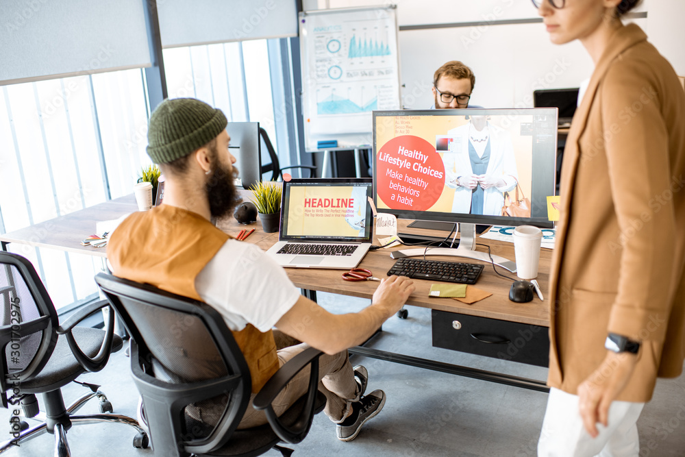 Group of diverse creative people working as a web designers in the modern office. Image focused on the computer screen with design
