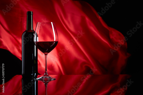 Wineglass and bottle of red wine on a black reflective background Canvas Print