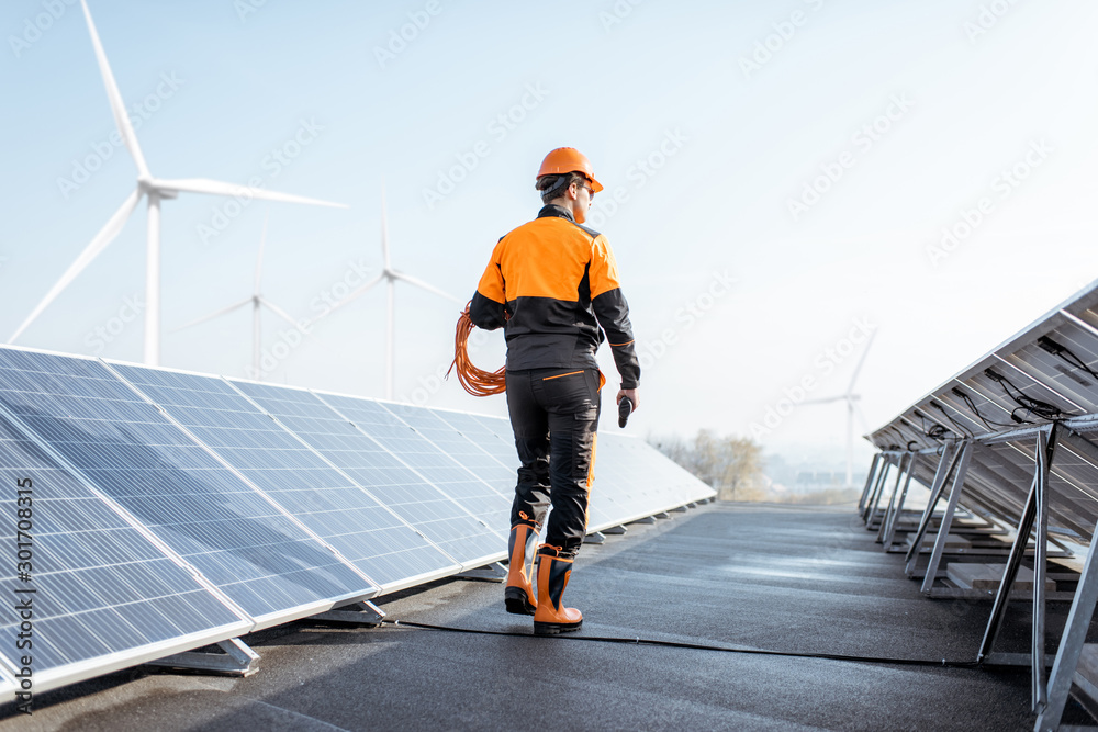 Fototapety, obrazy: Well-equipped worker in protective orange clothing walking and examining solar panels on a photovoltaic rooftop plant. Concept of maintenance and installation of solar stations