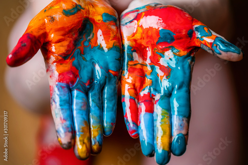 Obraz Closeup of woman hands dirty with acrylic paint. Creative finger painting. - fototapety do salonu