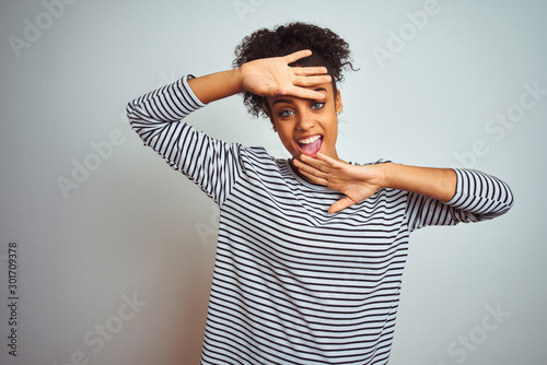 Vászonkép  African american woman wearing navy striped t-shirt standing over isolated white background Smiling cheerful playing peek a boo with hands showing face