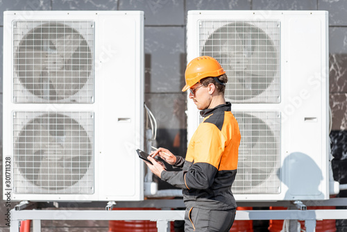 Workman servicing air conditioning or heat pump with digital tablet Canvas
