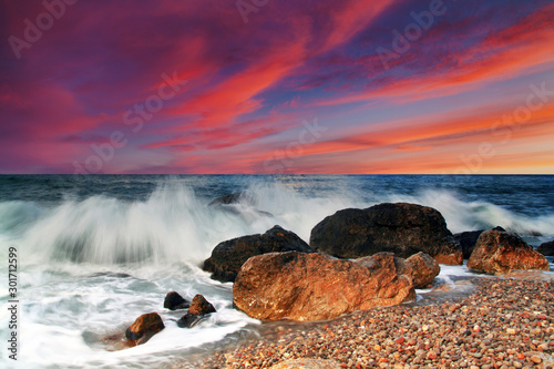 Foto auf Gartenposter Hochrote Sunset on the rocky shore of tropical sea