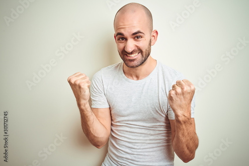 Stampa su Tela Young bald man with beard wearing casual white t-shirt over isolated background very happy and excited doing winner gesture with arms raised, smiling and screaming for success