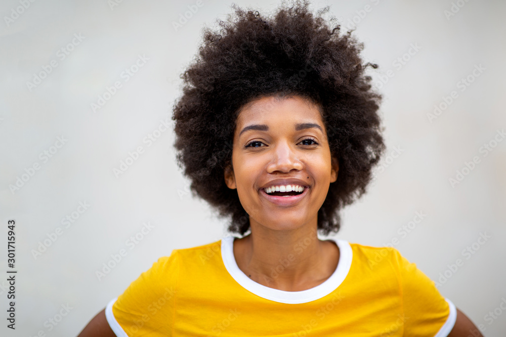 Fototapeta Close up of beautiful young black afro woman smiling by white background