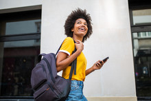 Happy Young Black Woman Walking Outside With Cellphone And Bag
