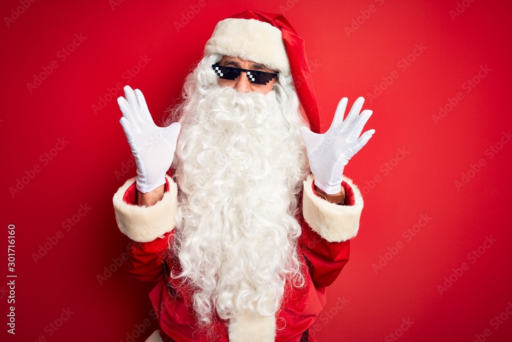Fototapety, obrazy: Middle age man wearing Santa Claus costume and sunglasses over isolated red background celebrating crazy and amazed for success with arms raised and open eyes screaming excited. Winner concept