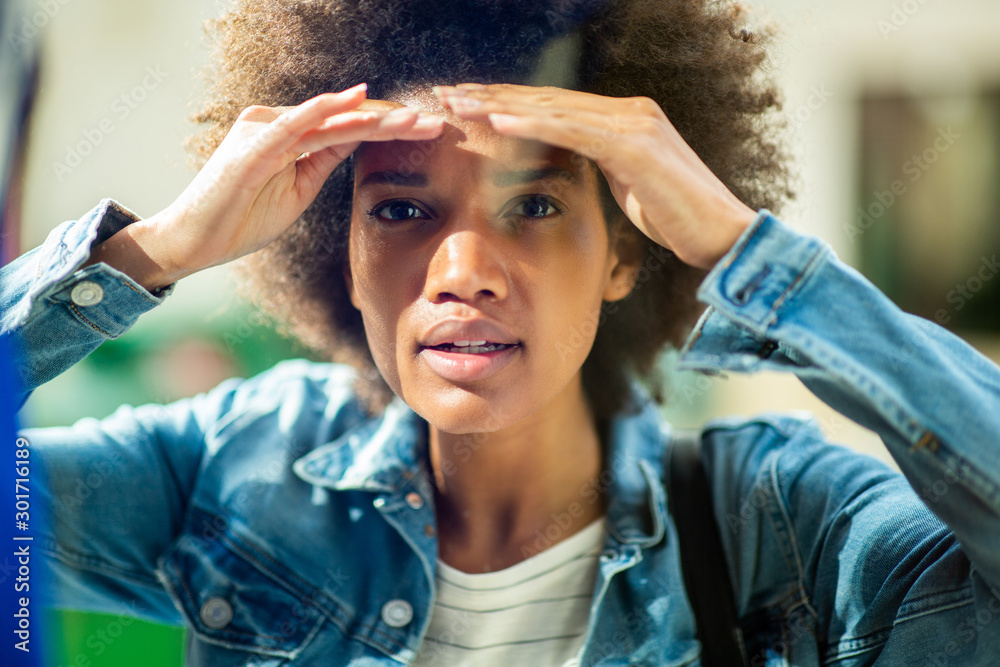 Fototapeta Close up of young african american woman peeking through window