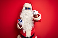Senior Man Wearing Santa Claus Costume Using Smartphone Over Isolated Red Background Pointing With Finger To The Camera And To You, Hand Sign, Positive And Confident Gesture From The Front