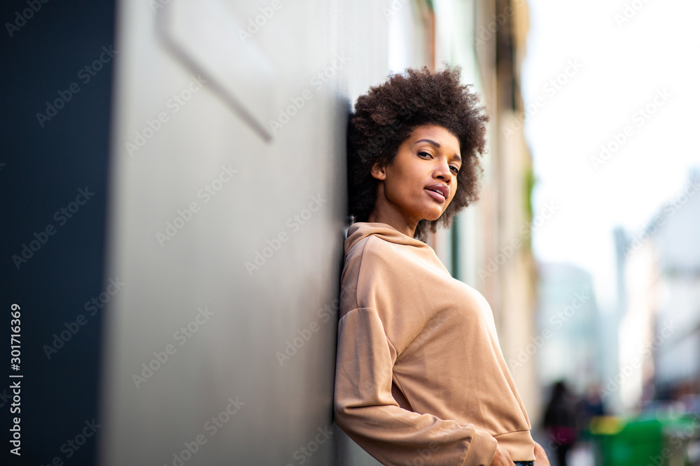 Fototapeta beautiful black female fashion model with afro hairstyle leaning against wall