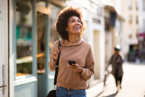 obraz dibond happy young black woman with phone walking in city