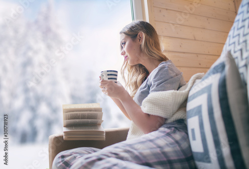 Foto auf Leinwand Lachs Young beautiful blonde woman with cup of coffee sitting home in living room by the window. Winter snow landscape view. Christmas concept