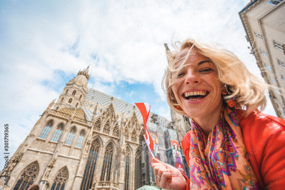 Fototapety, obrazy: Woman stands on the background of St. Stephen's Cathedral in Vienna with the flag of Austria in hand, Austria