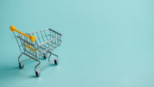 Shopping Cart On Blue Background. Supermarket Shop Trolley As Sale, Discount, Shopaholism Concept With Copy Space For Text Or Design.