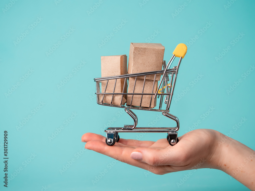 Fototapeta Toy shopping cart with boxes in female hand over blue background. Copy space for text or design. Ssale, discount, shopaholism concept. Consumer society trend