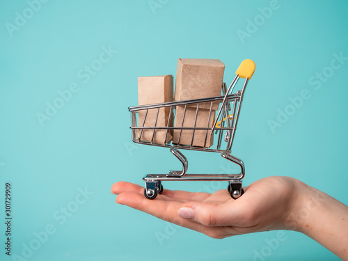 Fototapeta Toy shopping cart with boxes in female hand over blue background. Copy space for text or design. Ssale, discount, shopaholism concept. Consumer society trend obraz