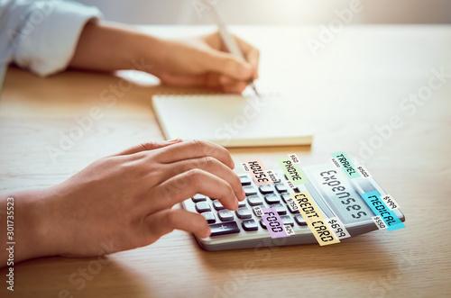 Woman press calculator to calculate income expenses and plans for spending money on home office Tapéta, Fotótapéta
