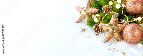 Fototapeta Gold vintage Christmas and New Year Decoration isolated on white background. Border art design with holiday baubles. Beautiful Xmas tree closeup decorated with balls, tinsel, cones. Space for text obraz