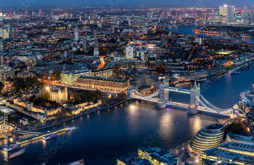 Poster Londres Blick auf die beleuchtete Skyline von London am Abend mit Tower Bridge und modernen Bürogebäuden entlang der Themse
