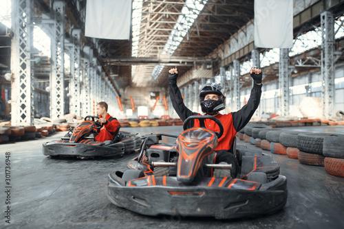 Fotografie, Obraz Go kart racer raised his hands up, front view