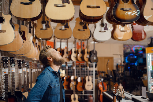 Fotografía Young guy choosing acoustic guitar in music store
