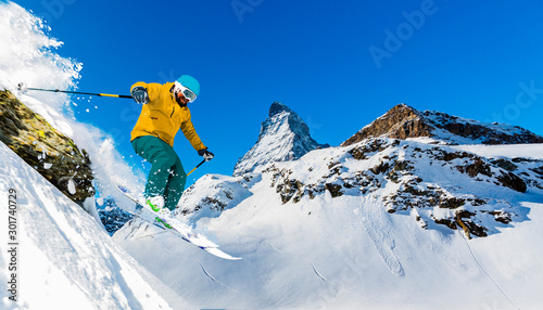 Photo Man skiing on fresh powder snow with Matterhorn in background, Zermatt in Swiss Alps