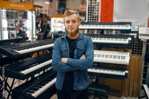 Door stickers Music store Young man choosing synthesizer in music store