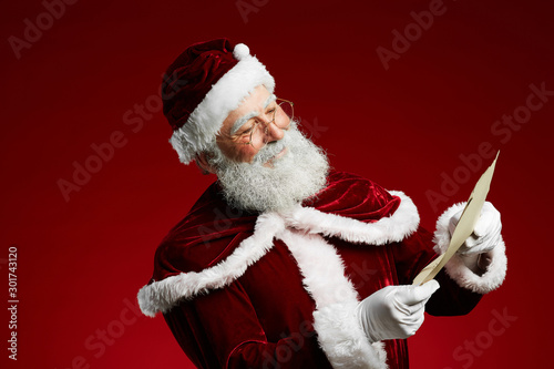 Waist up portrait of smiling Santa reading list on parchment standing against re Fotobehang