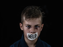 """Portrait Of A Scared Beaten Up Boy Victim Of Domestic Violence And Abuse With Covered His Mouth Taped With The Inscription """"help"""". Isolated On Dark Background"""