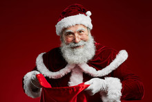 Waist Up Portrait Of Smiling Santa Claus Holding Sack With Christmas Presents While Standing Over Red Background, Copy Space