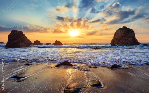Obraz Sand beach among rocks on evening sunset. Ursa Beach near Cape Roca (Cabo da Roca) at Atlantic Ocean coast in Portugal. Summer landscape. - fototapety do salonu