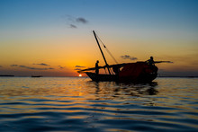 Traditional Fisherman Dhow Boat During Sunset On Indian Ocean In Island Zanzibar, Tanzania, East Africa