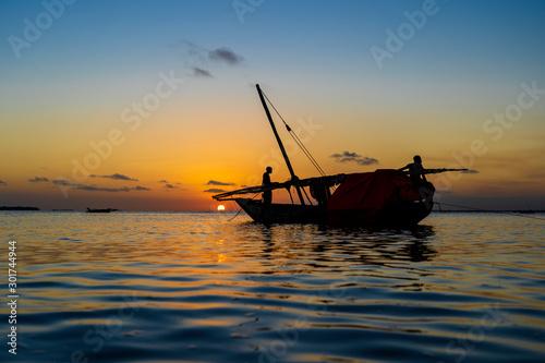 Foto auf AluDibond Afrika Traditional fisherman dhow boat during sunset on Indian ocean in island Zanzibar, Tanzania, East Africa