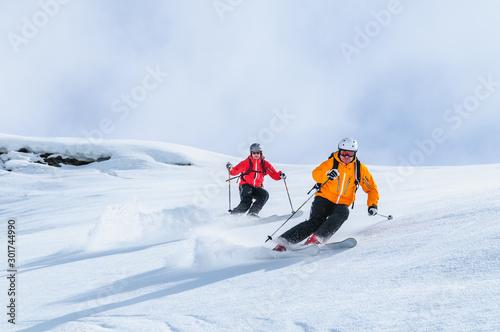 Photo Zwei Skifahrer befahren gemeinsam einen steilen Hang