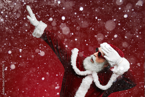 Waist up portrait of cool Santa dancing over red background with snow falling, copy space