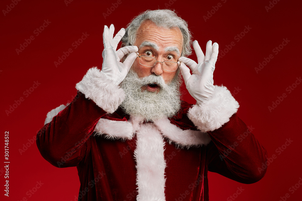 Fototapeta Waist up portrait of surprised Santa Claus looking at camera and adjusting glasses while posing against red background in studio, copy space