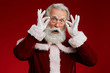 canvas print picture - Waist up portrait of surprised Santa Claus looking at camera and adjusting glasses while posing against red background in studio, copy space