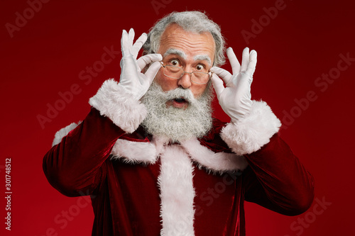 Waist up portrait of surprised Santa Claus looking at camera and adjusting glass Tablou Canvas