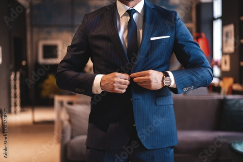 Handsome man adjusting his jacket while standing in modern office Wallpaper Mural
