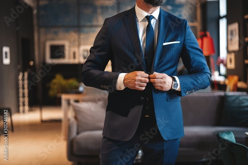 Handsome man adjusting his jacket while standing in modern office.