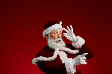 Waist Up Portrait Of Surprised Santa Claus Pointing To Side And Adjusting Glasses While Posing Against Red Background In Studio, Copy Space