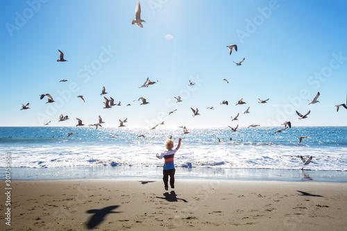 Obraz na płótnie Happy and free boy on the beach with seagulls
