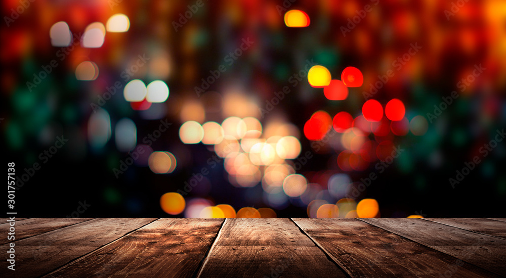 Fototapeta Wooden table, blurred bokeh background background. Neon light, night view, close-up. The general background of the interior, a dark background.