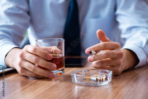 Male employee drinking alcohol and smoking cigarettes at workpla Wallpaper Mural