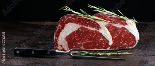Raw fresh meat Ribeye Steak, seasoning and meat fork on rustic background Fototapet