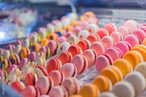 Tuinposter Bakkerij Dessert, biscuit, sweet food and traditional french cuisine concept. Assortment of colorful macarons cakes for sale on counter of candy shop, market, cafe or bakery. Rows of bright colors macaroons.